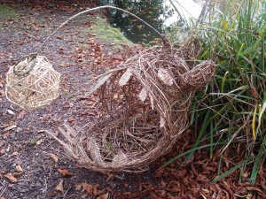 photo of large willow anfgler fish sculpture sitting next to pond